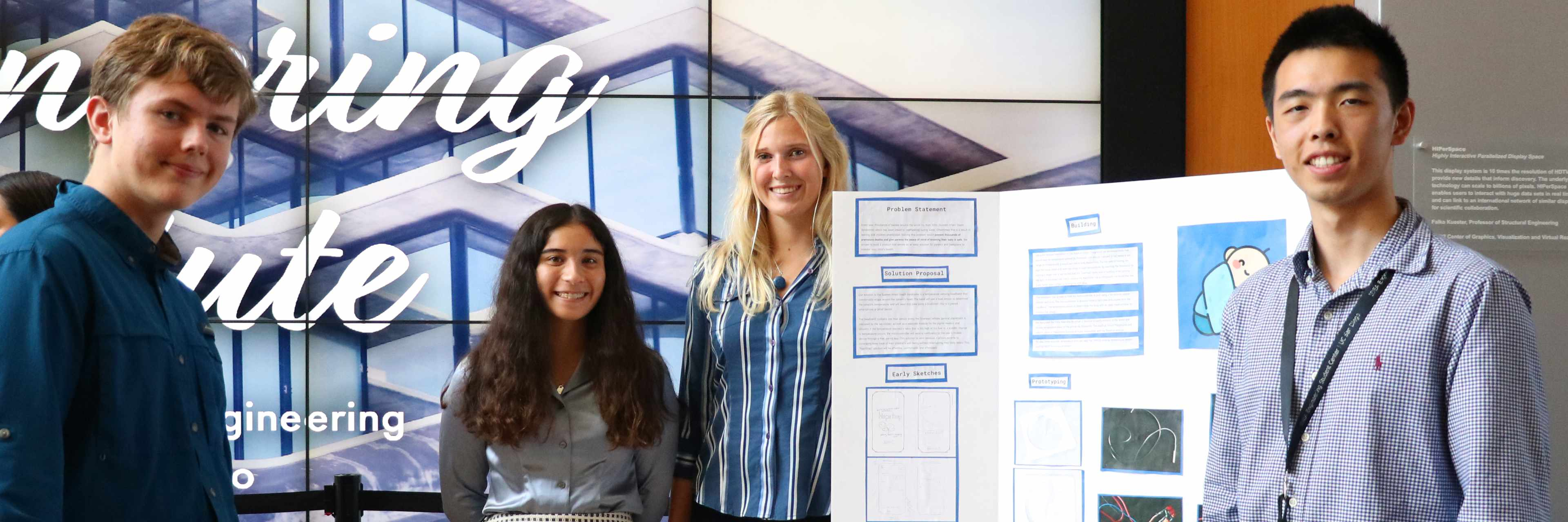 Four students standing next to poster